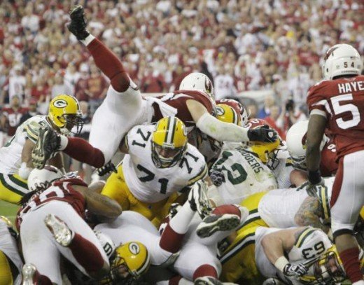 Green Bay Packers quarterback Aaron Rodgers (12) sneaks into the end zone for a touchdown during the first half of an NFL wild-card playoff football game against the Arizona Cardinals on Sunday, Jan. 10, 2010, in Glendale, Ariz. (AP Photo/Ross D. Fra