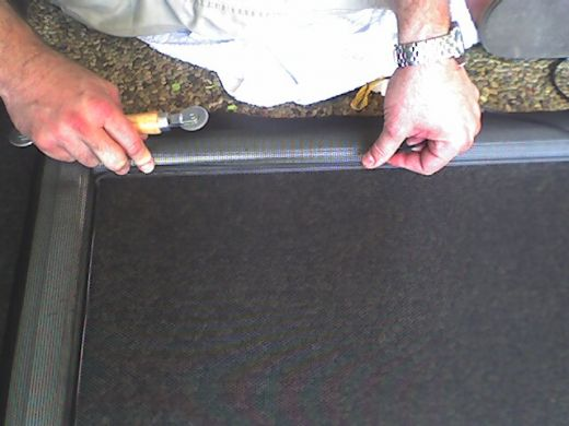 Lay the spline aroung the groove of the sliding door.  If it's hard to push the spline in the groove, stretch it out a bit and then roll it in.  Also pull the screen tight when you are pushing in the spline on the opposite side.  You may need a helpe