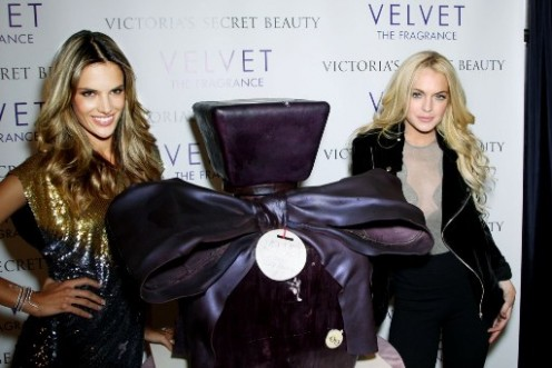 Lindsay Lohan pokes a hole into VS Velvet's perfume cake with her hand as press watches on.
