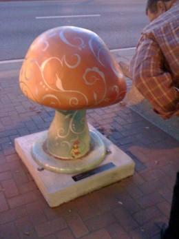 Mushroom statue on the sidewalk.