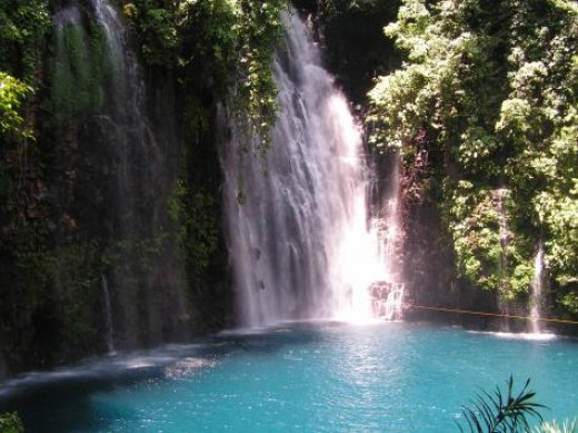 Tinago Falls in Iligan City, Lanao del Norte, Philippines. Tinago means hidden, very appropriate for a hidden gem of a waterfall. The waterfall is surrounded by steep cliffs and drops into a deep blue pool perfect for a cool swim.