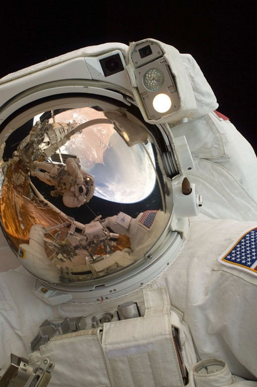 NASA - reflection of astronauts working on the Hubble Space Telescope.