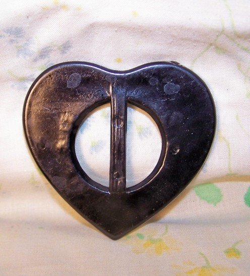 Back view of black plastic heart slide. In very good shape, none to minimal wear to be seen.