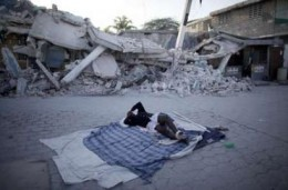 A woman tries to sleep near the devastation caused by the earthquake.