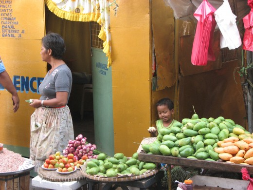 A vendor selling mangos and tomatoes as her son takes a snack.