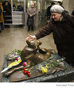 A commuter stops to pet the statue erected to the memory of Malchik.
