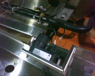This image shows the control panel pulled off the gas grill.  The module is mounted in the control panel.  Electrode wires, valves and manifold for gas grill is also visible.