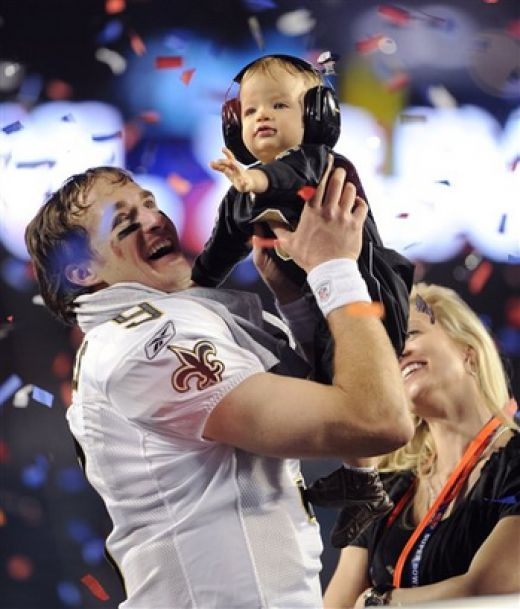AP  New Orleans Saints quarterback Drew Brees celebrates with his son Baylen and wife Brittany after winning the Super Bowl.