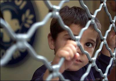 Small immigrant child looking out from behind the fence of T. Don Hutto Prison