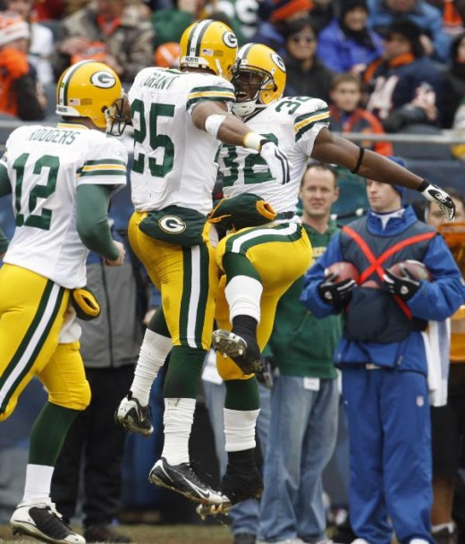 Green Bay Packers running back Ryan Grant (25) celebrates his touchdown with teammate Brandon Jackson (32) as Packers quarterback Aaron Rodgers (12) passes them during the first half of an NFL football game against the Chicago Bears in Chicago, Sunda