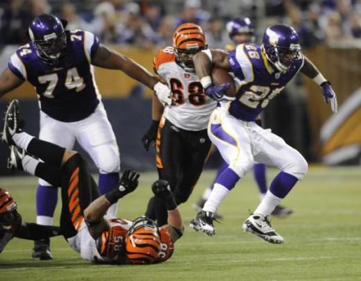 Minnesota Vikings' Adrian Peterson runs past Cincinnati Bengals' Rey Maualuga (58) during the first half of an NFL football game Sunday, Dec. 13, 2009, in Minneapolis. (AP Photo/Hannah Foslien)