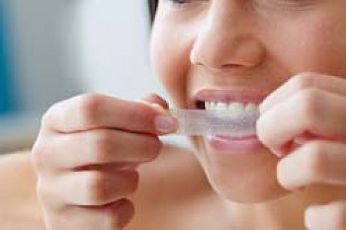 Consumer using tooth whitening strips