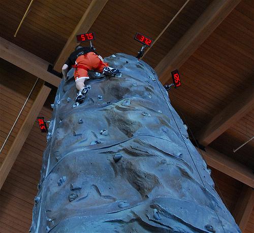 A man climbing an artificial rock wall.