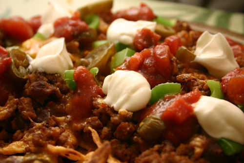 home-style nachos with sharp cheddar, refried beans, meat, and a bunch of toppings