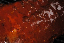 Ribs on the grill coated with the mop sauce. The vinegar in the sauce helps tenderize the meat and keeps it succulent.