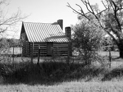 Black and White photo of a rare, double chimney log cabin that has been restored. Very rare to see one with two chimneys!