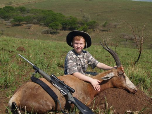 Authors son with a record class Blesbuck.  Note the use of natural surroundings to pose the trophy.  No shadows, clean natural background, etc.