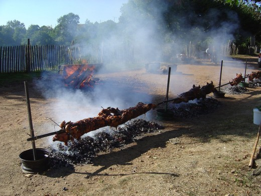 Smoke and the scent of roasting pork fill the air.