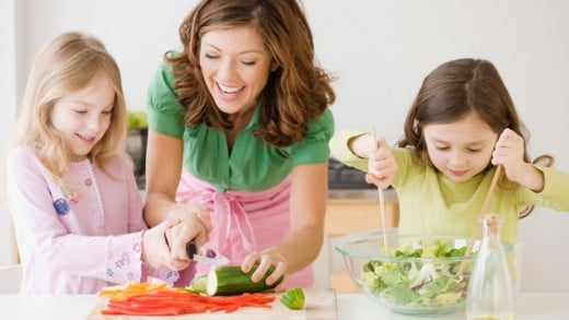mom and kids preparing meal, just be careful when using knives with children in the kitchen
