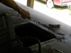 Removing old roof coating and sealants for a smooth, watertight seal.