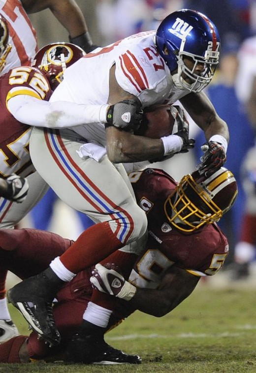 New York Giants running back Brandon Jacobs is tackled by Washington Redskins linebackers Rocky McIntosh, left, and London Fletcher during first quarter of an NFL football game, Monday, Dec. 21, 2009, in Landover, Md. (AP Photo/Nick Wass)