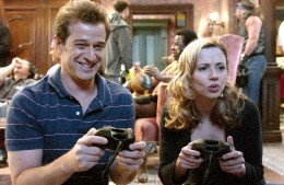 Alex and Samantha play a video game at a party.
