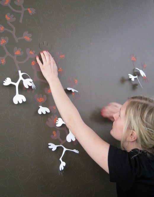 Hanna Nyman peeling off 3d wallpaper to reveal underlying design
