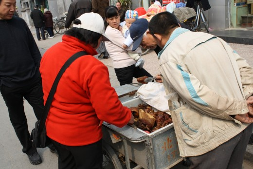Meat being sold from the back of a bike in a Hutong