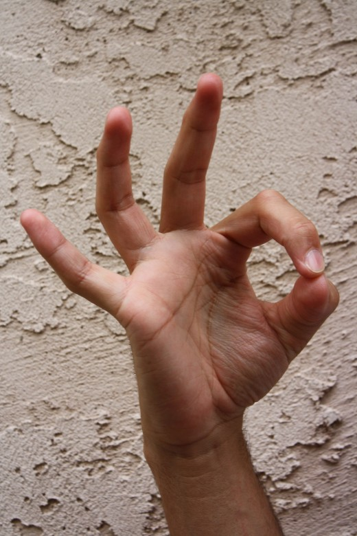 Index and thumb touch while remaining fingers are upright and spread apart.