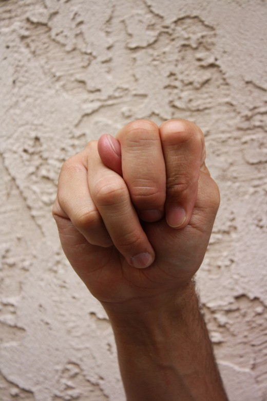 Closed fist with the thumb between the ring and middle fingers.