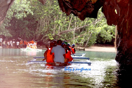 Paddle boat with tourists emerging from the cave and underground river