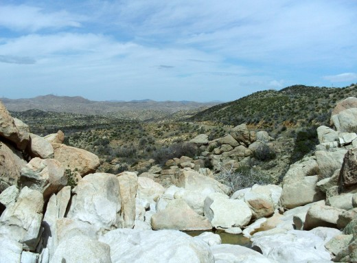 A glimpse of the small creek trickling between the large boulders.  The mountainous desert in the distance is full of chaparral, manzanita, and scrub brush.