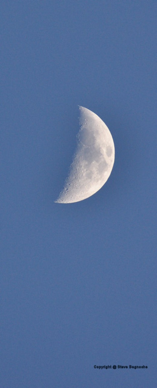 The moon is slightly to the west and overhead before sunset.