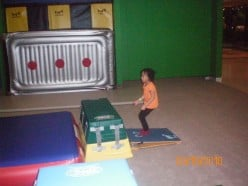 Learning how to use the vaulting board to jump over the mat mountain - side view.