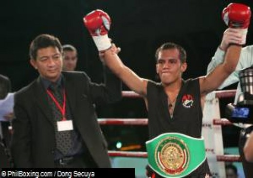 Filipino boxer Melindo (R)  raised gloves in victory after knocking out Thailander Komrith Twinsgym.  At left is Dr. Nasser Cruz, GAB Chief