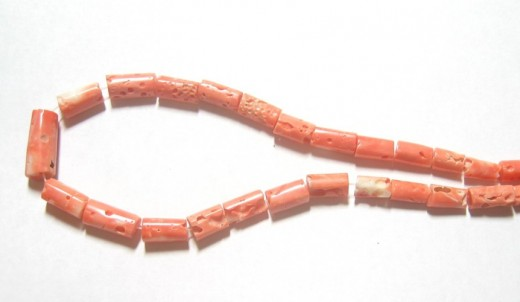 Lovely handcut coral beads in a tube/barrel shape. The color ranges from dark pink to salmon with splashes of white. They are not completely polished so they have areas that are rough and poreus. They have a great and unusual look.