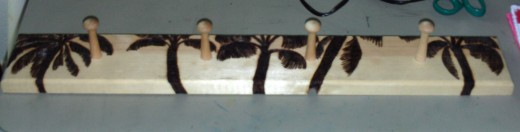 This picture shows how all of the palm trees are now burned on the coat rack, which will be used as a place to hang my necklaces.