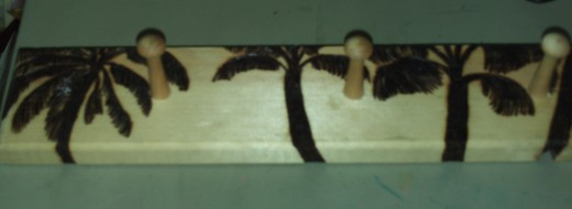 The wood burned palm trees on the left side of the jewelry rack.