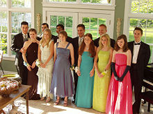 A typical gathering of students attending HS Prom, boys in tuxedos and girls in dresses with corsages in their wrists