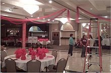 Students and advisers helping together decorate finishing touches in a ballroom of a banquet hall