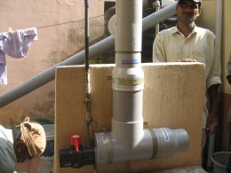 THE RAIN WATER FILTER IS FIXED ON THE SMALL WALL BETWEEN THE WELL AND THE PUMP USED TO PUMP WATER FROM BWSSB FROM A SINTEX PLASTIC TANK TO ANOTHER TANK ABOVE THE ROOF FOR DRINKING AND COOKING AS ALSO FOR BATH.