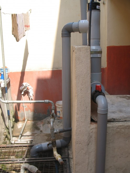 THE PICTURE SHOWS THE PVC PIPES FROM ABOVE TO THE WELL BELOW.
