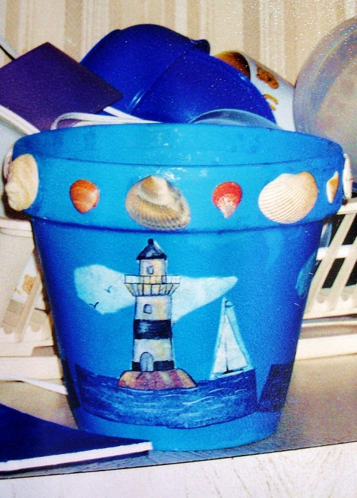 A students clay pot with lighthouse-oceanic theme