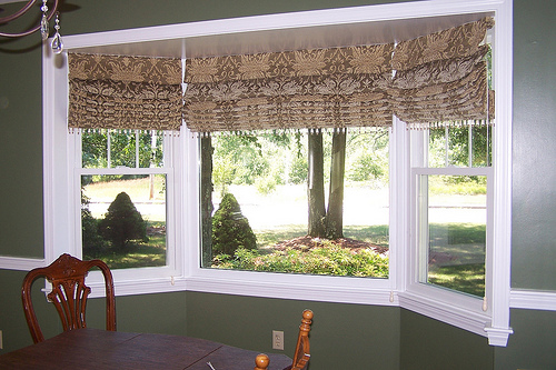 Roman shades are inexpensive and come in many designs, fabrics, and styles that will match your room.