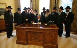With Chabad rabbis from across the world looking on, President George W. Bush signs a presidential proclamation in honor of the 2008 Education and Sharing Day, and highlighting the important work of the Chabad Lubavitch movement.