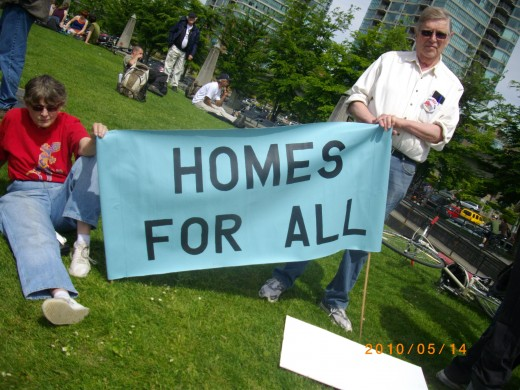 Two protesters ready their sign for the march to the Olympic condos.