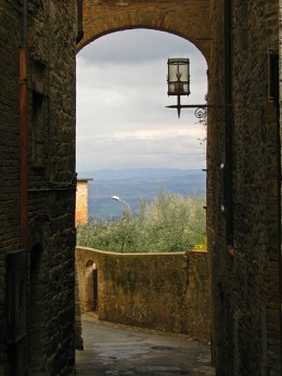 A wrought iron lamp sits in the archway overlooking the Tuscan countryside.