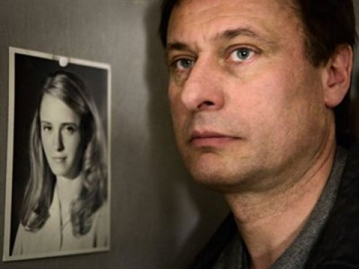 Michael Nyqvist as Mikael Blomqvist with photo of Harriet Vanger