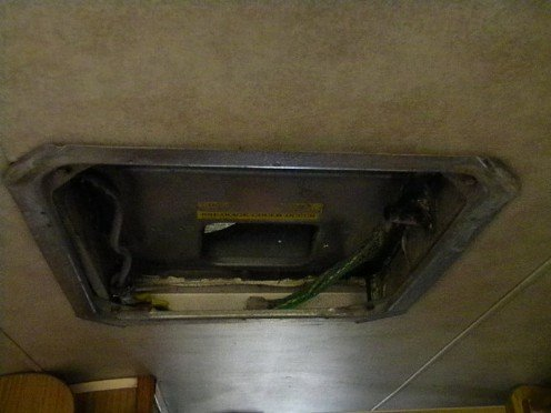 The RV AC tension bracket with retaining bolts and wiring exposed