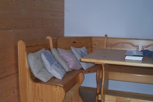 Wooden seats and table, with embroidered cushions to do jigsaw puzzles